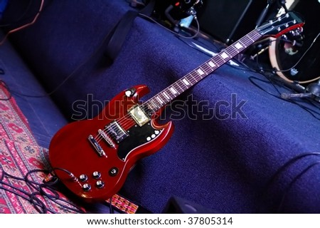 red electric guitar on scene - stock photo
