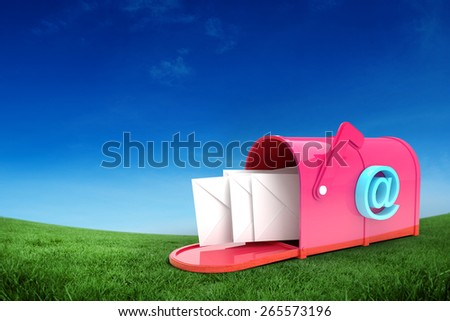 Red email postbox against green field under blue sky - stock photo