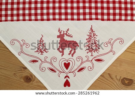Red embroidered deer, Christmas tree, heart  on white and checkered plaid linen fabric  tablecloth on wooden rustic background - stock photo
