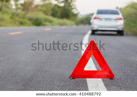 Red emergency stop sign and broken silver car on the road. - stock photo