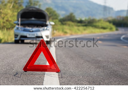 Red emergency stop sign and broken silver car on the road - stock photo