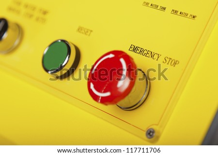 Red emergency stop switch and green reset button - stock photo