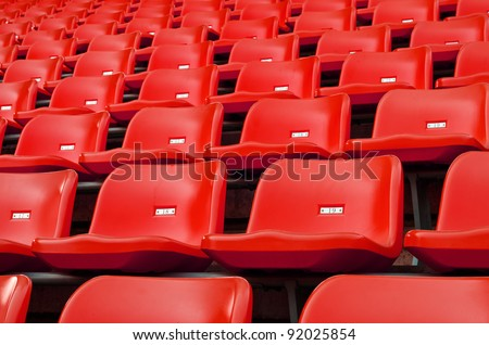 Red Empty plastic seats at stadium open door sports arena - stock photo