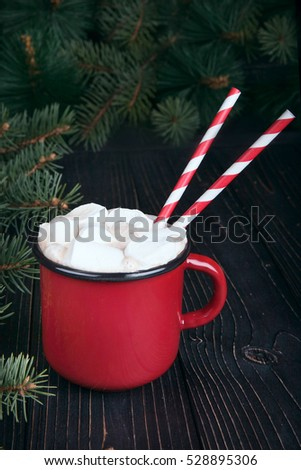 Red enamel cup of hot cocoa with marshmallows on dark wooden bac