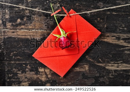 Red  envelop and rose  hanging on the clothesline. On old wood background - stock photo