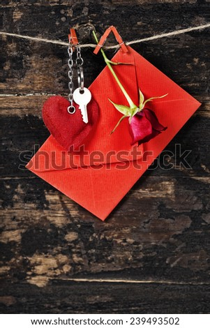 Red  envelop, key and rose  hanging on the clothesline. On old wood background - stock photo