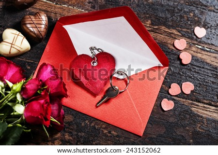 Red  envelop, roses, chocolate and key On old wood background - stock photo