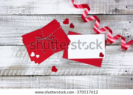 Red envelopes tied in string and white note card with scattered hearts and ribbon on white rustic antique wood background; Valentine's Day and love concept - stock photo