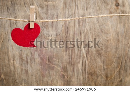 Red fabric heart hanging on the clothesline. On old wood background. - stock photo