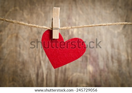 Red fabric heart hanging on the clothesline. On old wood background.central location - stock photo