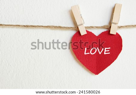 Red fabric heart with love word hanging on the clothesline, valentine background template  - stock photo