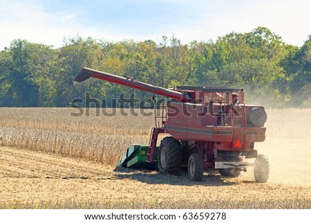 Red farm combine harvesting a soybean crop - stock photo