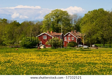 Red farm house on the field - stock photo