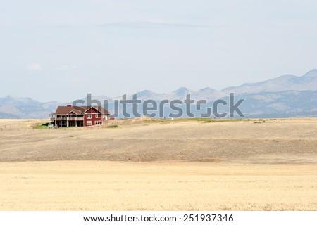 Red farmhouse with Montana mountains on background - stock photo