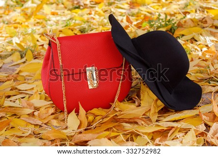 Red fashionable leather handbag and black hat with wide brim autumn style - stock photo