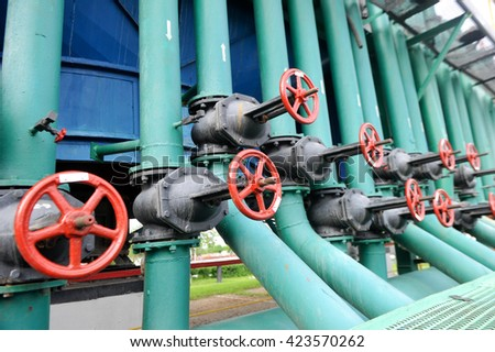 Red faucet with steel pipe in natural gas compressor station in summer day - stock photo
