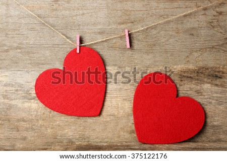 Red felt hearts hang on cord against wooden background - stock photo