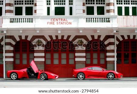 Red Ferrari Enzo and F430 in front of Fire Station Singapore - stock photo