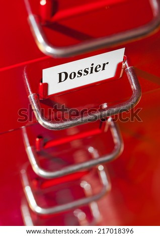Red file cabinet with card Dossier - business background - stock photo
