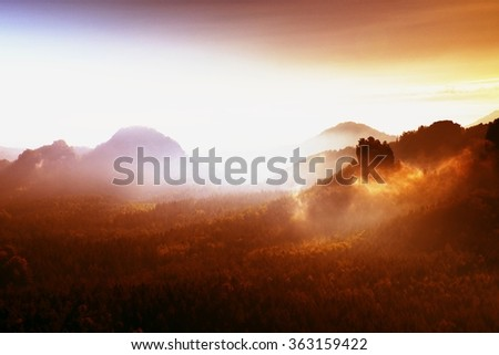Red filter photo. Red daybreak. Misty daybreak in a beautiful hills. Peaks of hills are sticking out from foggy background, the fog is red and orange due to Sun rays.  - stock photo