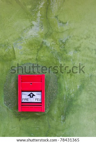 Red Fire alarm on green wall - stock photo
