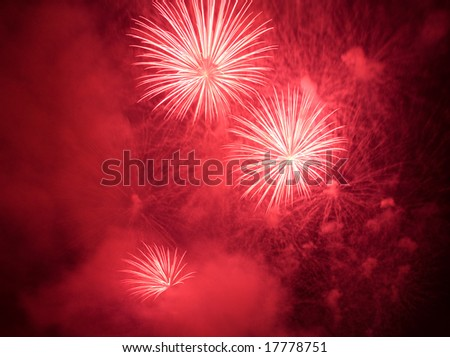 Red fireworks exploding in clouds of smoke - stock photo