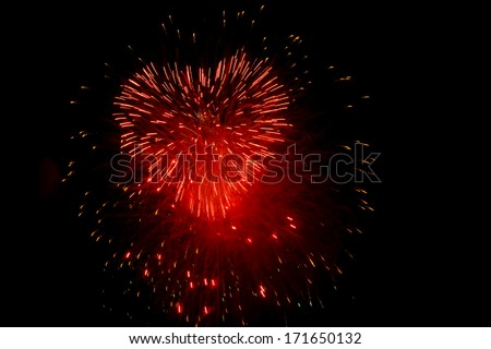 Red fireworks in the night sky in the form of heart