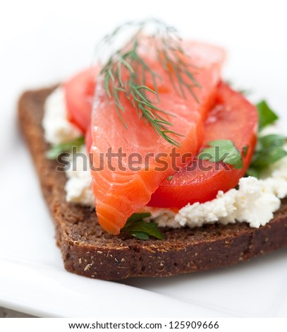 Red fish canape with cream cheese and tomato on white plate - stock photo