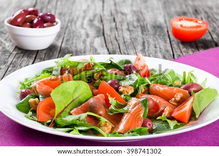 Red fish healthy salad with mixed lettuce leaves, olives and tomatoes on a white dish on a old rustic table, easy recipe, close-up - stock photo