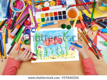 red fish underwater, crab on seabed, child drawing, top view hands with pencil painting picture on paper, artwork workplace - stock photo