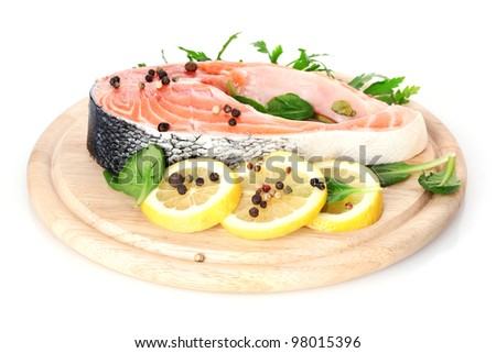 Red fish with lemon and parsley on wooden cutting board isolated on white - stock photo