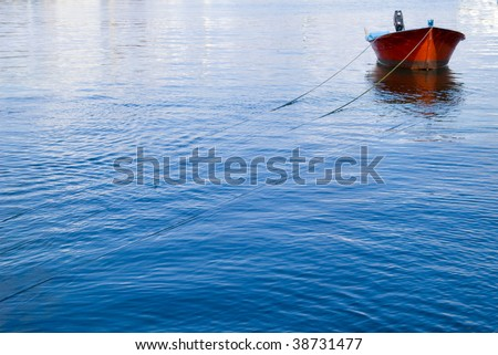 Red fishing boat in a sea blue.