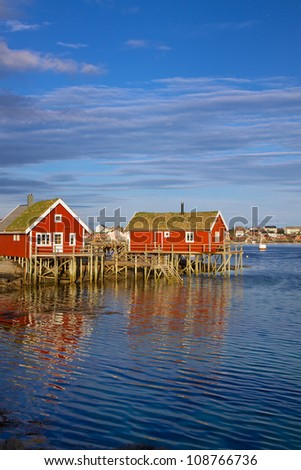 Red fishing rorbu huts by the fjord in town of Reine on Lofoten islands