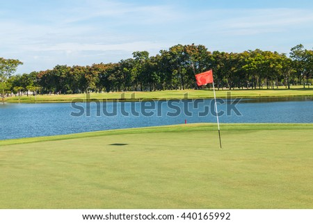 Red flag and sand bunker at the beautiful golf course at the lake side at sunset, sunrise time. Gorgeous view at the beautiful golf course with sand bunker and red flag. Golf course in Thailand. - stock photo