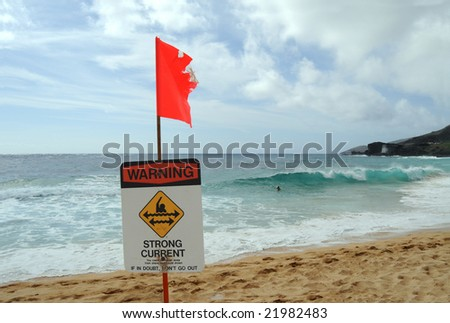 Red flag and warning sign on a dangerous beach in Hawaii. This particular sign was shot at Sandy Beach, a legendary bodysurfing location on Oahu, warning about strong currents. - stock photo