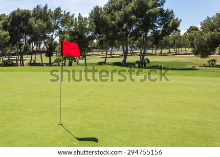 Red flag in the hole on a green golf field golf course - stock photo