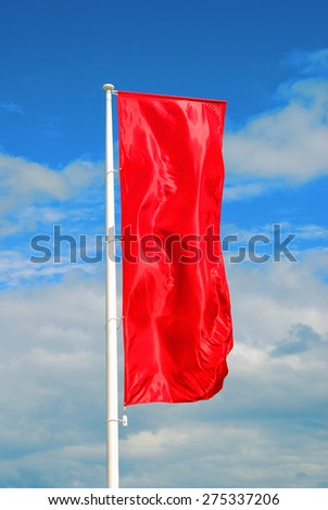Red flag waves under the wind. Blue sky with clouds background. No people. - stock photo
