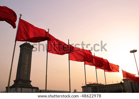 Red flags in Tian An Men Square, the left building is the Monument to the Peoples heroes.