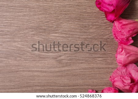 Red flowers lie on the wooden background. Space for text and design. Copyspace, top view