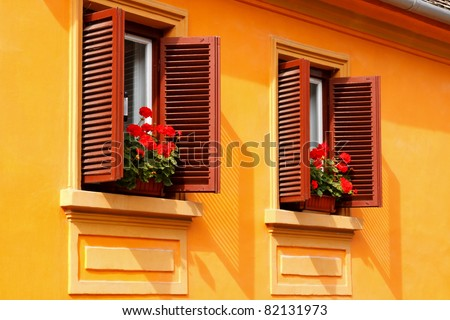 Red flowers on the windowsills of a yellow house - stock photo