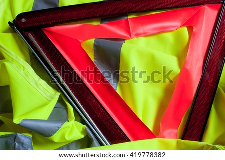 red fluorescent triangle and reflective of the vehicle stopped reporting for accident or damage and fluorescent yellow jacket with reflective stripes to wear in case of accident or damage to the road - stock photo