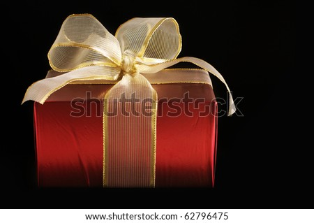 Red foil gift with golden bow on black background. - stock photo