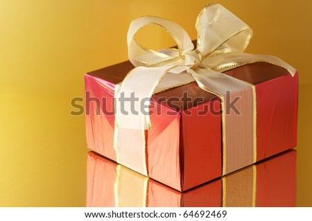 Red foil gift with golden bow on golden background with reflection. - stock photo