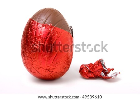 Red Foil wrapped chocolate easter egg isolated against white background - stock photo
