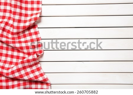 red folded tablecloth over bleached wooden table - stock photo