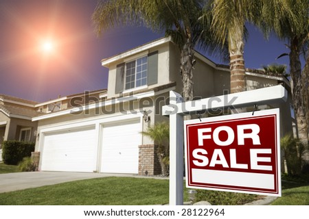 Red For Sale Real Estate Sign in Front of House with Red Star-burst in Sky. - stock photo