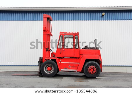 Red forklift truck by a warehouse.