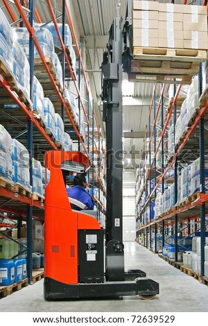 Red forklifter work in big warehouse