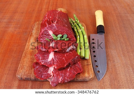 red fresh raw beef veal fillet with asparagus and stainless steel chef knife on cutting plate over wooden table prepared to use - stock photo