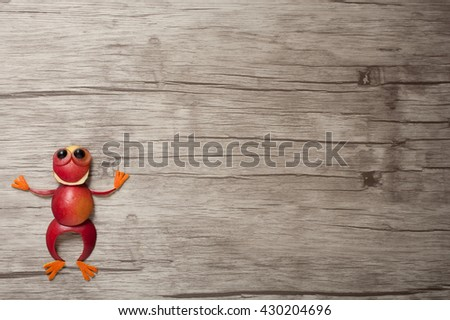 Red frog made of apple on wooden background - stock photo